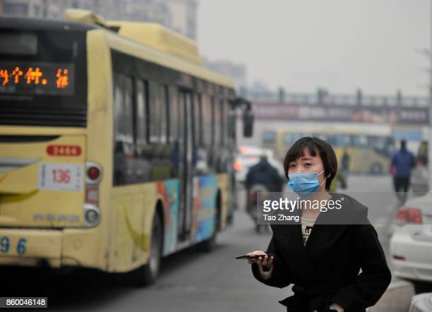 A woman wearing face masks walk past the building shrouded in severe Air Pollution on October 11 2017 in Harbin ChinaThe blue alert which is the most...