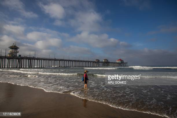 TOPSHOT A woman wearing face masks watches the ocean in Huntington Beach California on May 02 2020 Orange County beaches will remain closed after a...