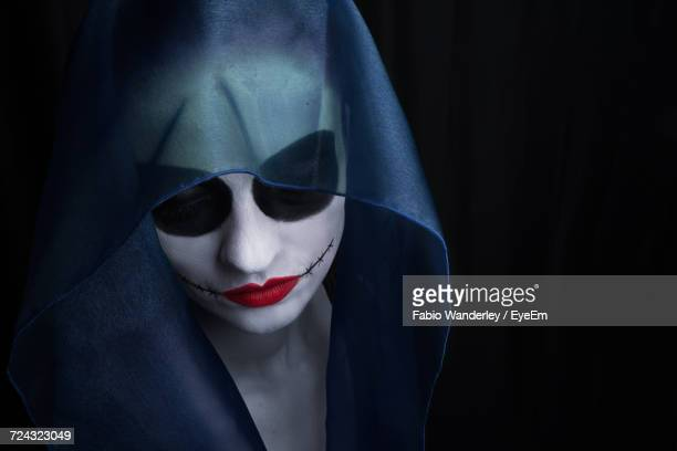 Woman Wearing Face Paint Against Black Background