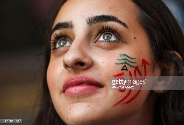 "Woman wearing facepaint depicting a Lebanese cedar tree and the Arabic word ""revolution"" looks on during a demonstration on the sixth day of protest..."