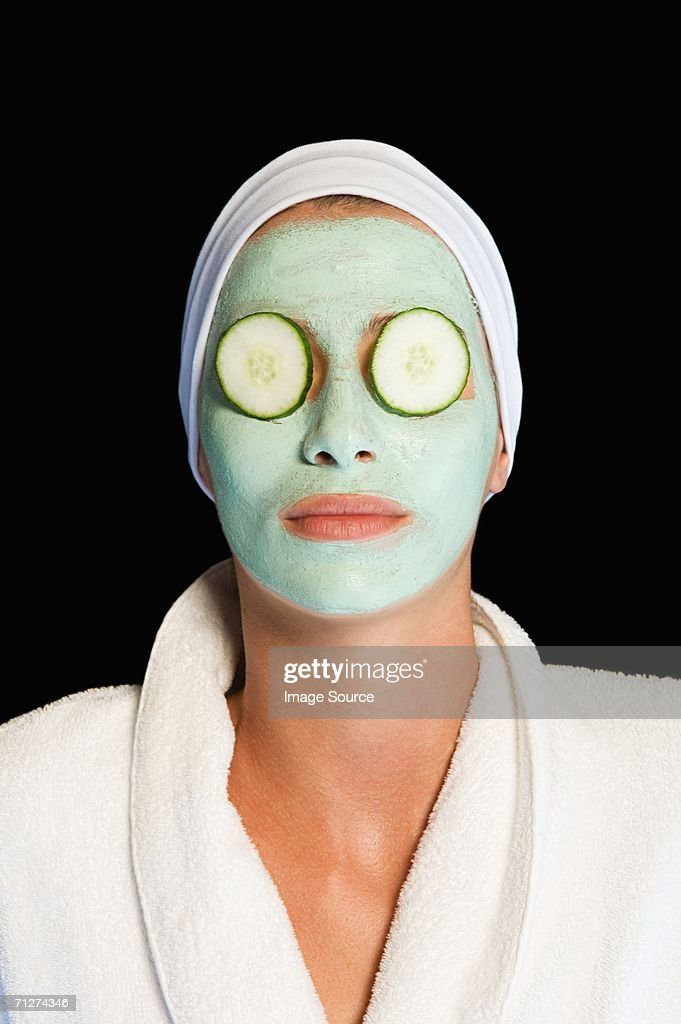 Woman wearing facial mask and cucumber slices : Stock-Foto