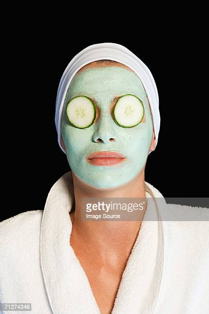 Woman wearing facial mask and cucumber slices