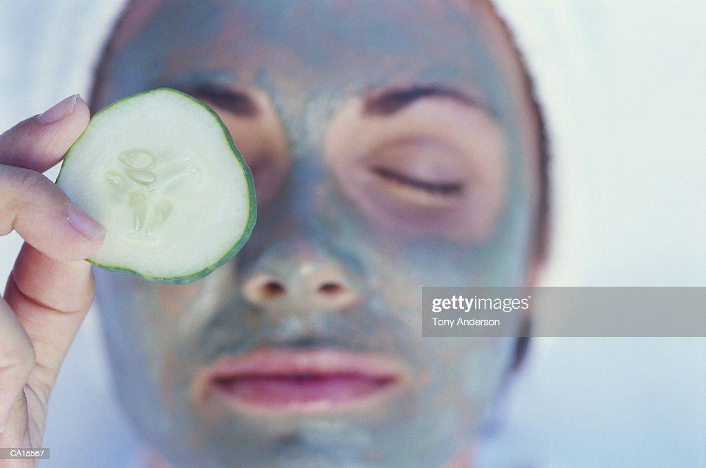 Woman wearing facial mask, putting cucumber slice on eye, close-up