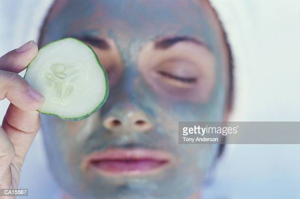 Woman wearing facial mask, putting cucumber slice on eye, close-up