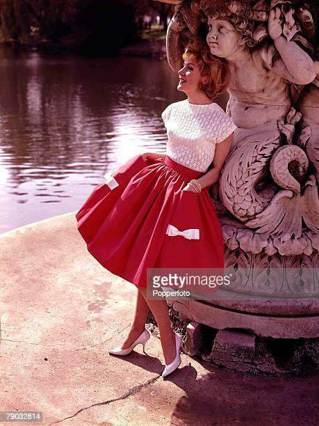 1961 A woman wearing fashionable daywear models an outfit consisting of a white sleeveless top and red billowing skirt decorated with white bows as...