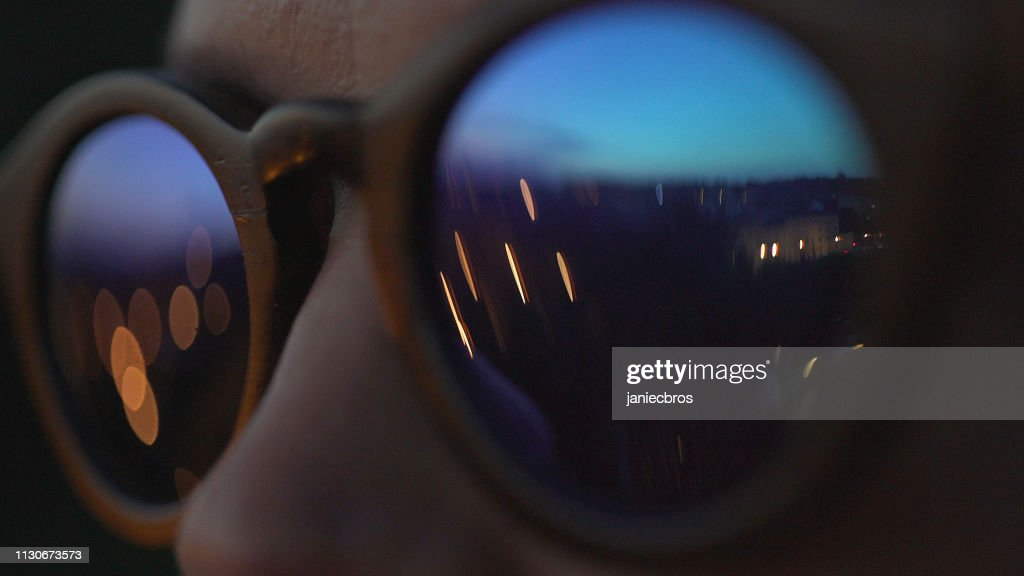 Woman wearing fashionable eyewear. City lights reflecting in glasses : Stock Photo