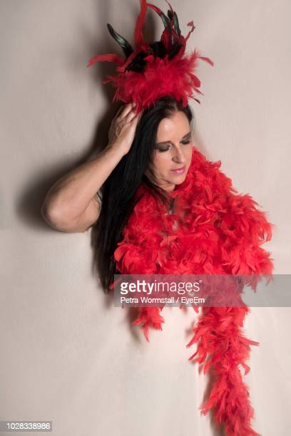 woman wearing feather boa against white background - feather boa stock pictures, royalty-free photos & images
