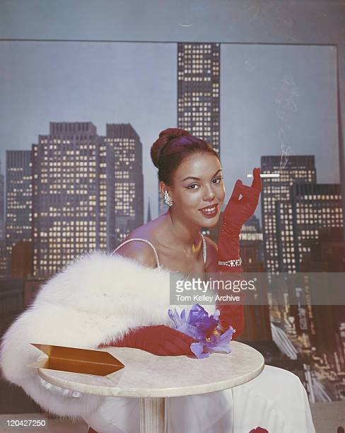 Woman wearing feather boa sitting with cigarette in hand, portrait