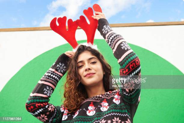 woman wearing festive antlers and christmas sweater - christmas jumper stockfoto's en -beelden