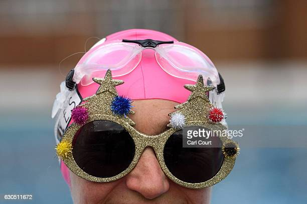 A woman wearing festive goggles poses for a photograph before entering the pool for a Christmas Day swim at Brockwell Lido on December 25 2016 in...