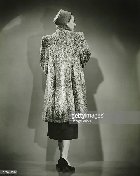 Woman wearing fir coat posing in studio (Rear view), (B&W)