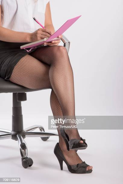 Woman wearing fishnet tights and a notebook on her knee