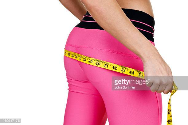 Woman wearing fitness clothing measuring her buttocks