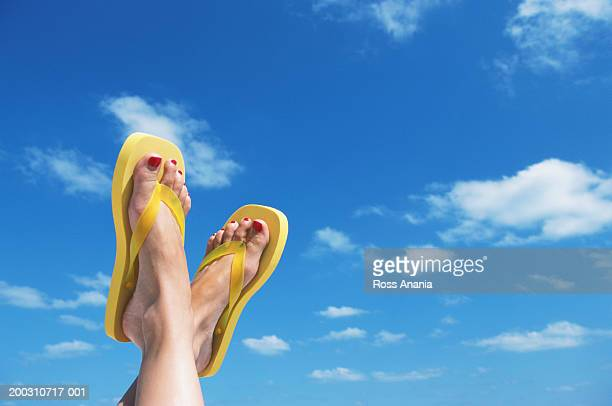 woman wearing flip-flops, feet up against sky, close-up of feet - ビーチサンダル ストックフォトと画像