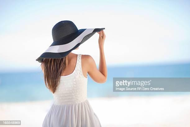 Woman wearing floppy hat on beach