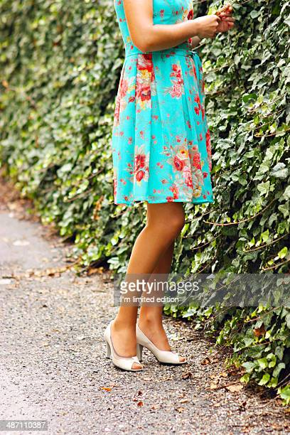 Woman wearing floral dress near ivy wall