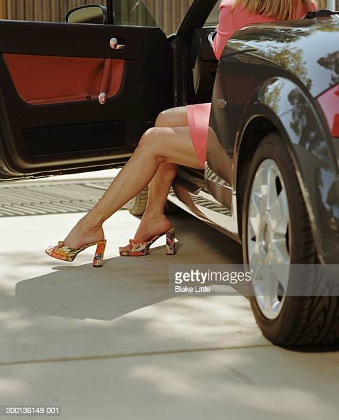 woman wearing floral print high heels, getting out of car, rear view - woman open legs stock photos and pictures