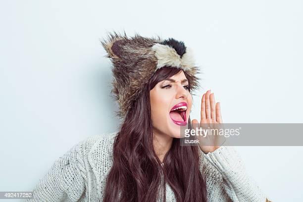 Woman wearing fur cap and sweater screaming