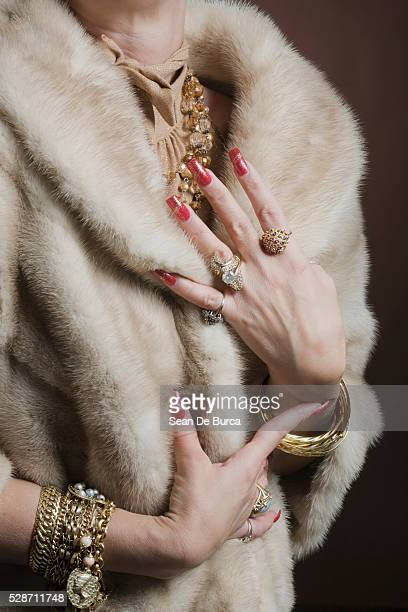 woman wearing fur coat and jewelry - fur coat stock pictures, royalty-free photos & images