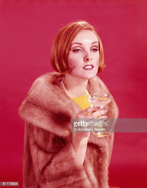 Woman wearing fur coat, holding glass of champagne. (Photo by H. Armstrong Roberts/Retrofile/Getty Images)