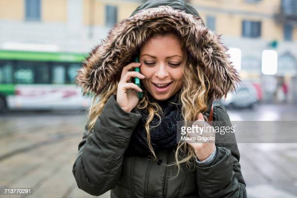 woman wearing fur trim hooded coat making telephone call smiling - fur trim stock pictures, royalty-free photos & images