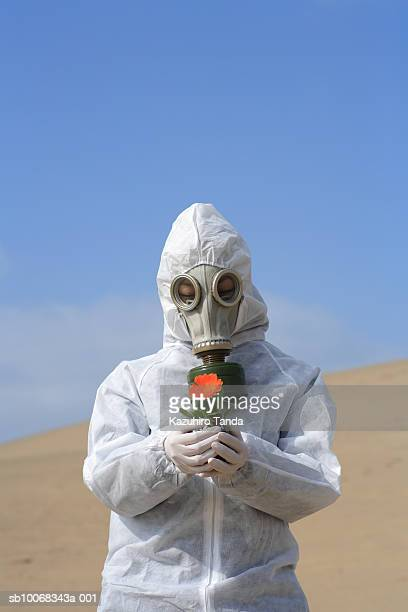 Woman wearing gas mask with flower in hand
