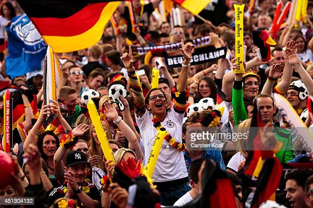 A woman wearing german national colors jumps surrounded by german fans celebrating while they watch the FIFA World Cup 2014 group G football match...