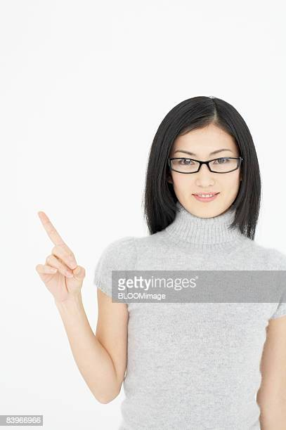 Woman wearing glasses, pointing