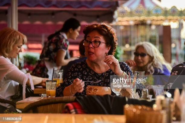 a woman wearing glasses sitting at an outdoor restaurant table and eating a soup with a spoon near red square in moscow, russia - sergio amiti stock pictures, royalty-free photos & images