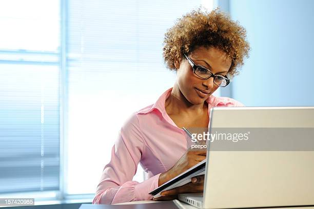 woman wearing glasses working on a laptop