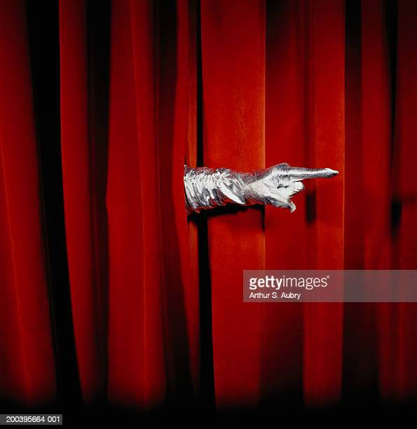 Woman wearing glove, pointing finger through curtain