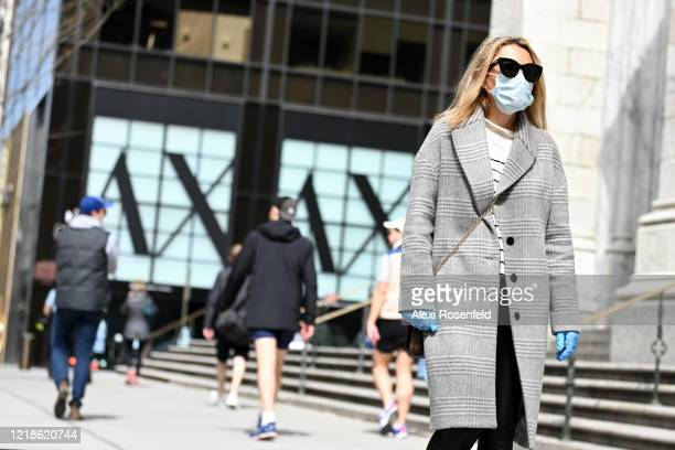 A woman wearing gloves and a protective mask walks along Fifth Avenue amid the coronavirus pandemic on April 12 2020 in New York City United States...