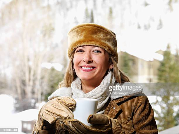 Woman wearing gloves and hat with hot beverage