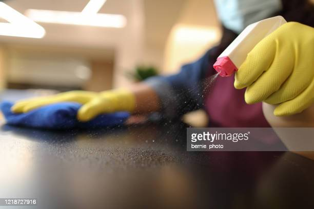 woman wearing gloves cleaning desktop - clean stock pictures, royalty-free photos & images