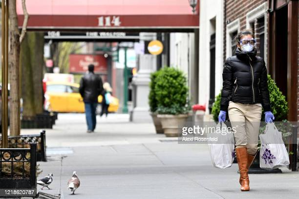 A woman wearing gloves goggles and a protective mask carries her groceries amid the coronavirus pandemic on April 12 2020 in New York City United...