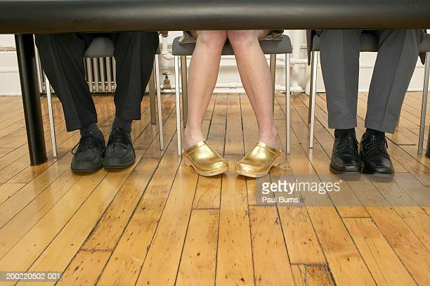 Woman wearing gold clogs sitting at desk between two men, low section