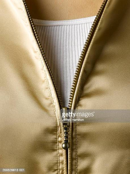 Woman wearing gold hooded sweatshirt with zip, close-up (full frame)