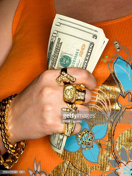 woman wearing gold jewellery, holding us dollar banknotes, mid section - bling bling stock pictures, royalty-free photos & images