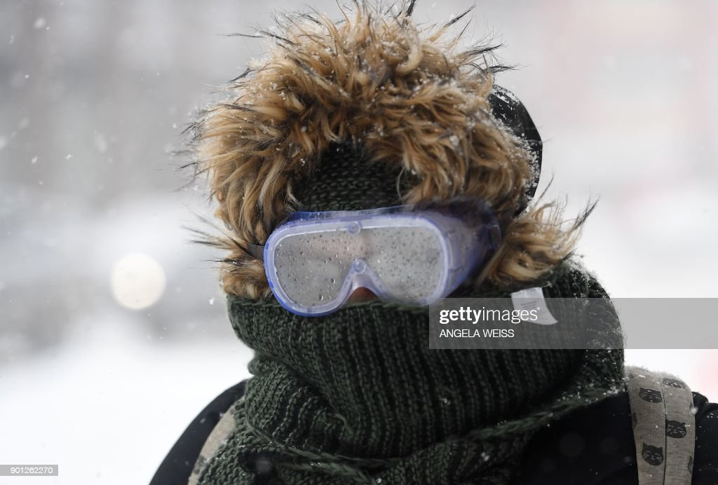 TOPSHOT - A woman wearing googles walks through the snow on January 4, 2018 in Brooklyn, New York. A giant winter 'bomb cyclone' walloped the US East Coast on Thursday with freezing cold and heavy snow, forcing thousands of flight cancellations and widespread school closures -- and even prompting the US Senate to cancel votes for the rest of the week.Millions of Americans faced potential power outages in bitterly cold sub-freezing temperatures, with some 45,000 people in Virginia and thousands more in Georgia, South Carolina and Florida already affected. WEISS