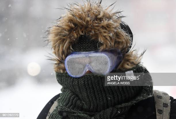 TOPSHOT A woman wearing googles walks through the snow on January 4 2018 in Brooklyn New York A giant winter bomb cyclone walloped the US East Coast...