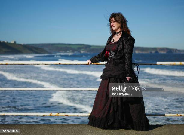 Woman wearing Gothic Victoriana clothing stands against railings on the pier during the Whitby Goth Weekend on October 27, 2017 in Whitby, England....