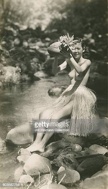 Woman wearing grass skirt and holding pineapple sitting on rocks in stream