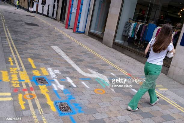 Woman wearing green trousers walks over multi-coloured aerosol-sprayed markings on the ground in a side-street off Long Acre near Covent Garden, are...