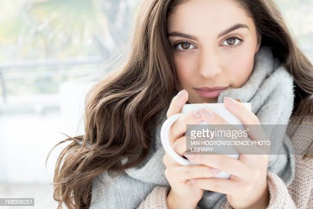 woman wearing grey scarf holding mug - tea hot drink stock pictures, royalty-free photos & images