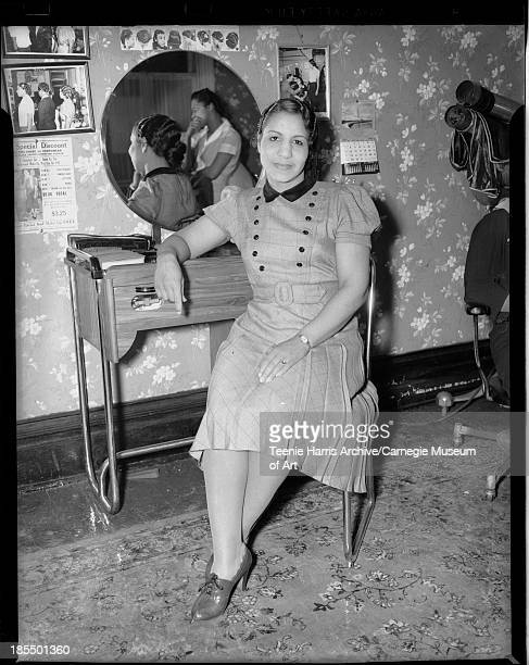 Woman wearing grid patterned dress with dark collar pleated skirt and two rows of dark buttons on bodice seated at beauty salon station with...