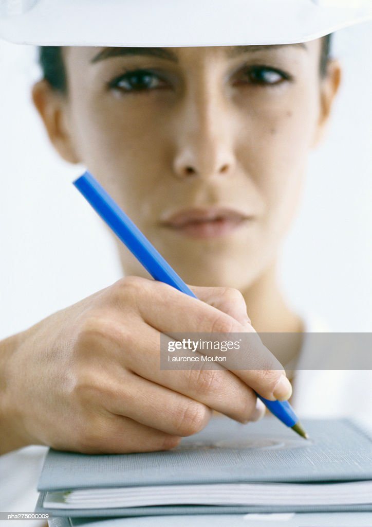 Woman wearing hard hat and holding pen, close-up : Stockfoto