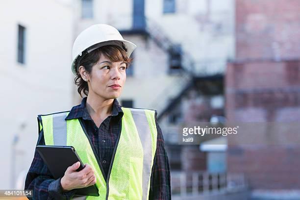 Woman wearing hard hat holding digital tablet