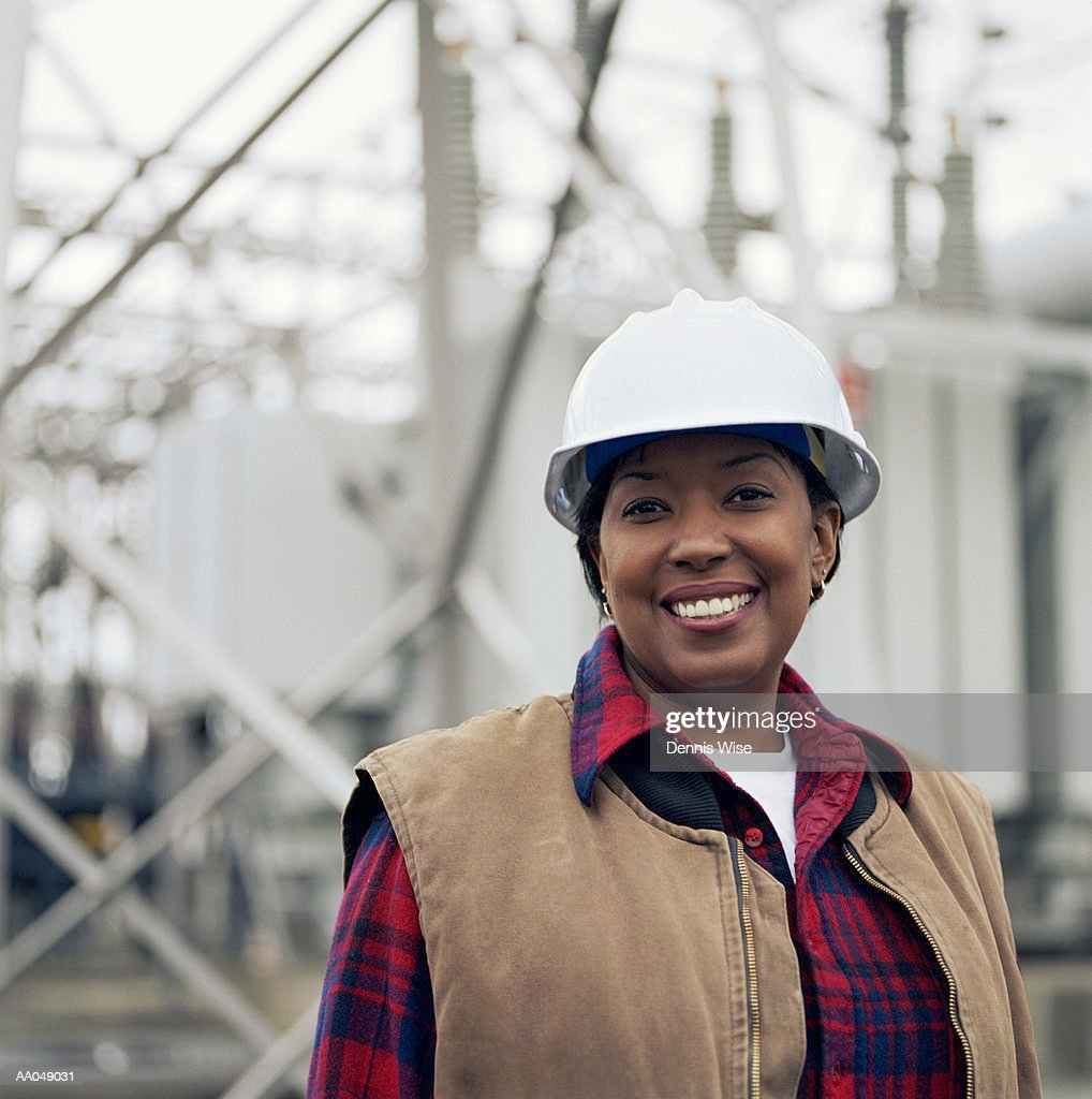 Woman wearing hard hat in front of power station, portrait : Stock Photo