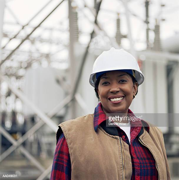 woman wearing hard hat in front of power station, portrait - power station stock pictures, royalty-free photos & images
