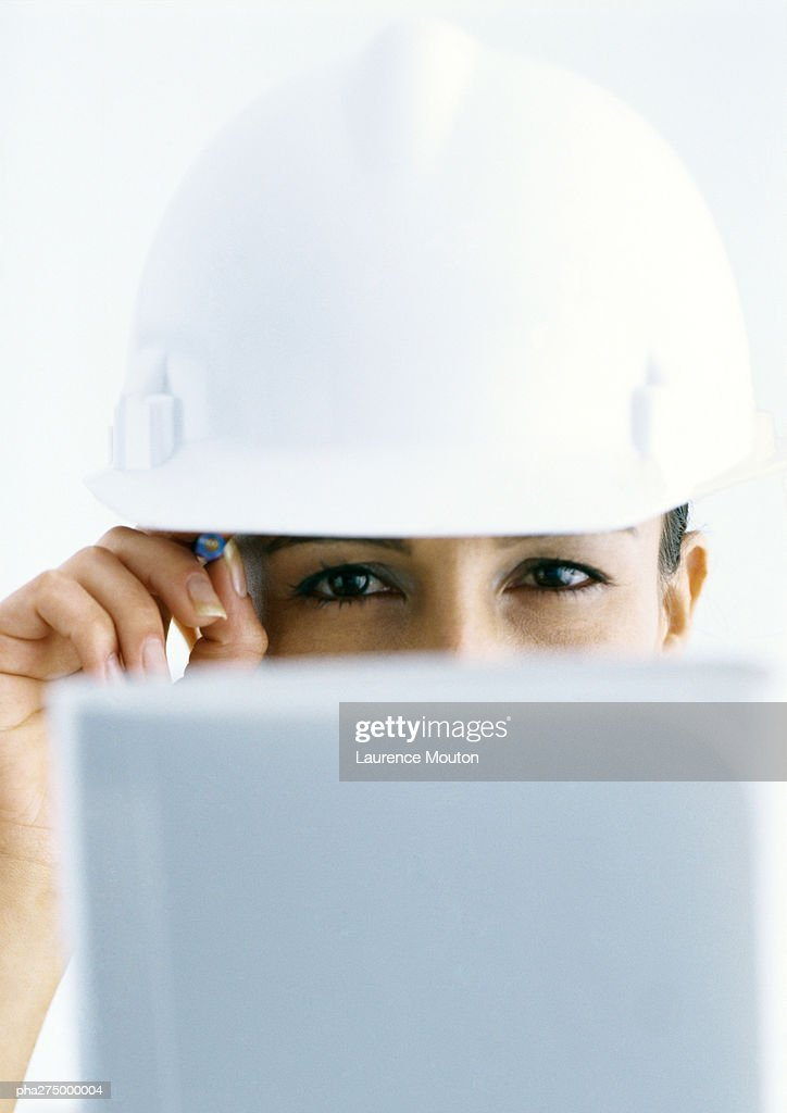 Woman wearing hard hat, looking over computer screen : Stockfoto